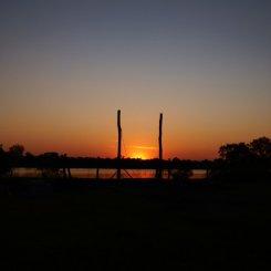 Sunset between the restaurant roof poles
